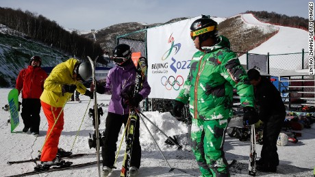Skiing enthusiasts stand in front of a sign for Beijing's bid for the 2022 Winter Olympics logo at a ski resort on January 17, 2015 in Zhangjiakou, Hebei Province, China.