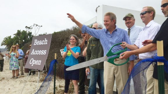 Steve Kinsey waves and Aaron McClendon and Charles Lester, right, wield giant scissors as the Coastal Commission officials formally open the path.