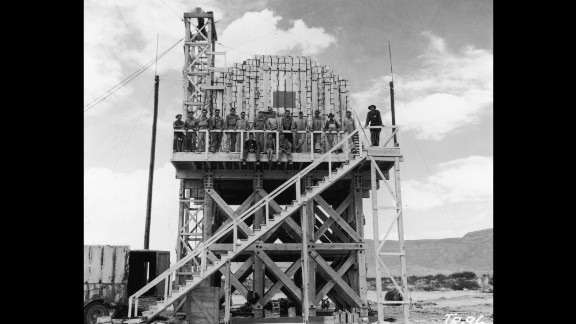 Los Alamos workers pose on a platform stacked with 100 tons of TNT. It was to be used to gauge radioactive fallout.