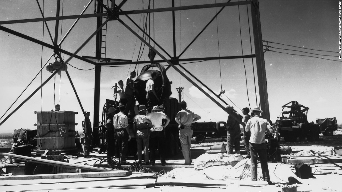 Workers in New Mexico attach a bomb to a tower two days before its successful test in July 1945.