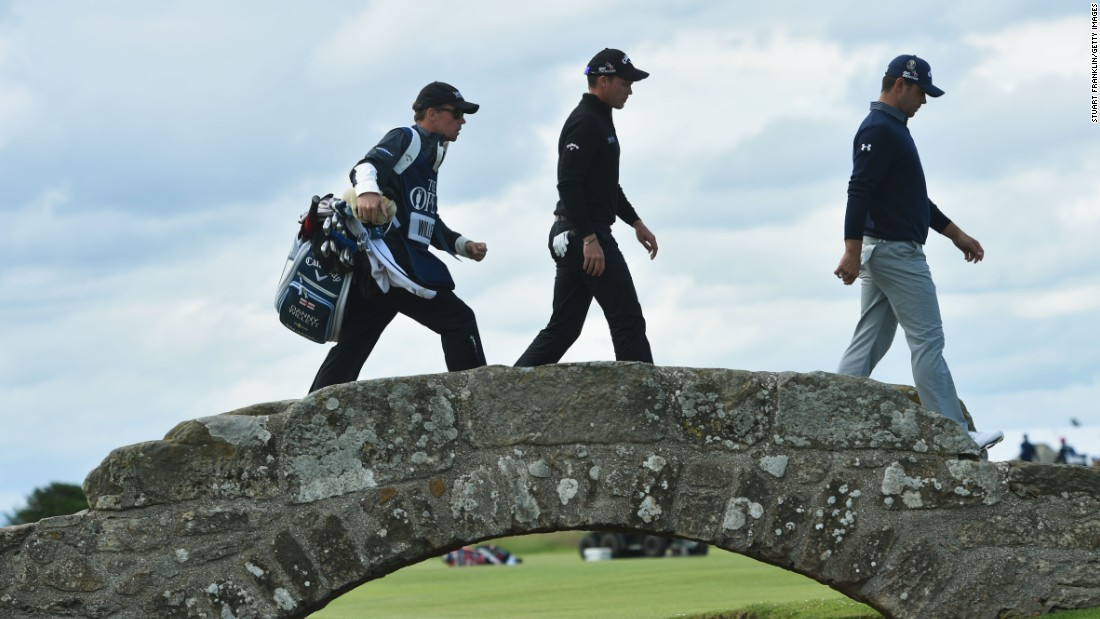 Gary Woodland of the United States (R), Danny Willett of England (C) and his caddie Jonathan Smart (L) walk across Swilcan Bridge.