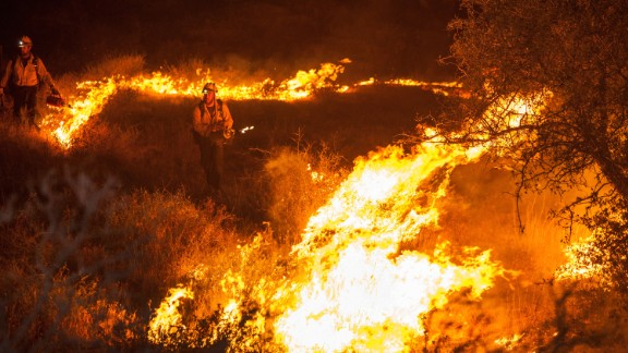 Firefighters start a backfire along Baldy Mesa Road late on July 17.
