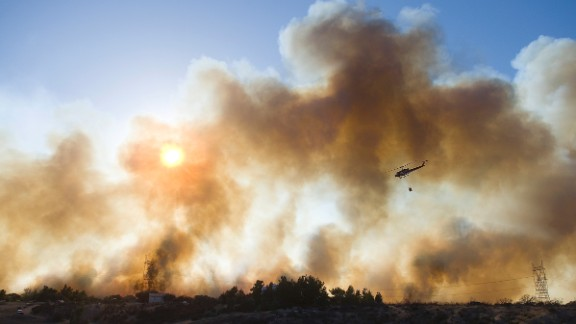 A helicopter prepares to drop water over a fire near Oak Hills, California, on July 17.