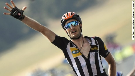 Great Britain's Stephen Cummings flashes the number five as he celebrates after crossing the finish line at the end of the 178,5 km fourteenth stage of the 102nd edition of the Tour de France cycling race on July 18, 2015, between Rodez and Mende, southern France. AFP PHOTO / ERIC FEFERBERG (Photo credit should read ERIC FEFERBERG/AFP/Getty Images