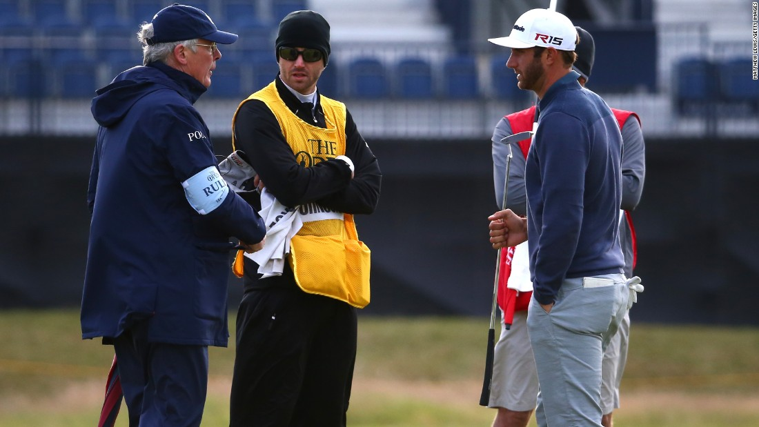Open Championship leader Dustin Johnson talks with a rules official on the 15th green as play is suspended due to high winds early on Saturday morning.