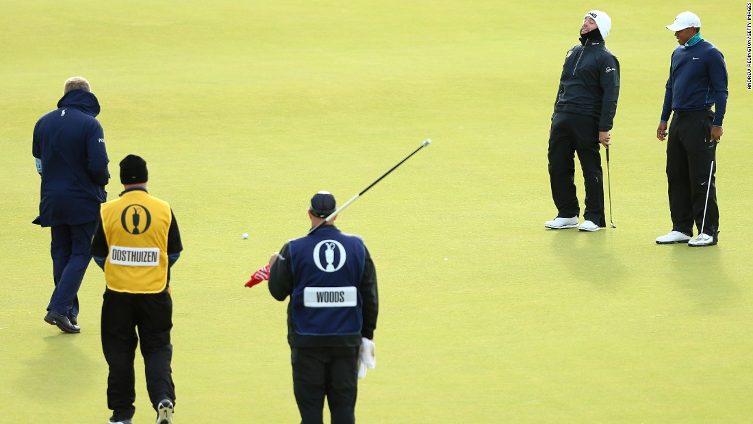 Louis Oosthuizen and Tiger Woods laugh as their balls move due to high winds on the 13th green before play is suspended during the second round at St. Andrews.