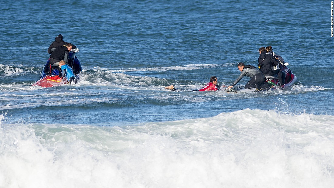 Fanning and Julian Wilson, in red, are rescued by personal watercraft.
