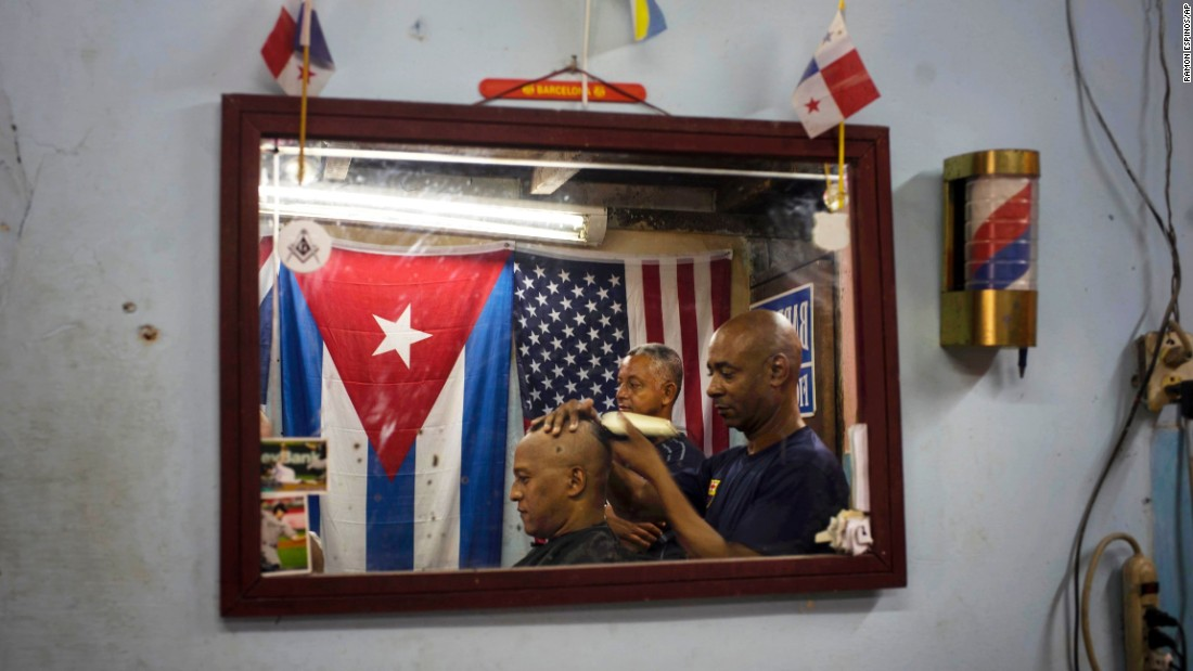 Eugenio Lafargue cuts a client's hair inside his barbershop in Havana on Saturday, July 18.