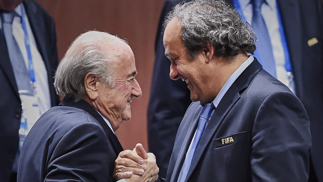 Caption:FIFA President Sepp Blatter (Foreground-L) shakes hands with UEFA president Michel Platini after being re-elected following a vote to decide on the FIFA presidency in Zurich on May 29, 2015. Sepp Blatter won the FIFA presidency for a fifth time after his challenger Prince Ali bin al Hussein withdrew just before a scheduled second round. AFP PHOTO / MICHAEL BUHOLZER (Photo credit should read MICHAEL BUHOLZER/AFP/Getty Images)