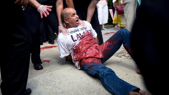 A demonstrator covered in red paint is detained after the flag-raising ceremony at the Cuban embassy in Washington.
