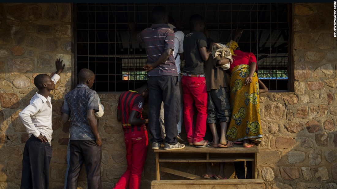 People watch through a window as voting officials count ballot papers in Mubimbi, Burundi, on July 21.