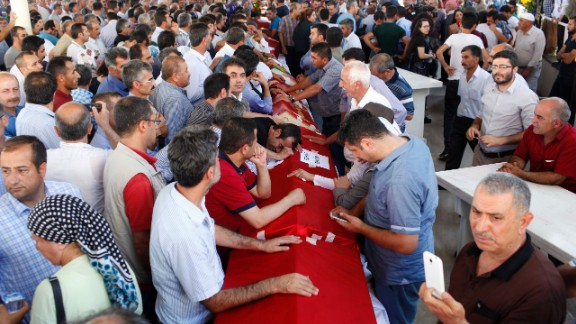 Turks mourn over coffins during a funeral for Suruc attack victims.