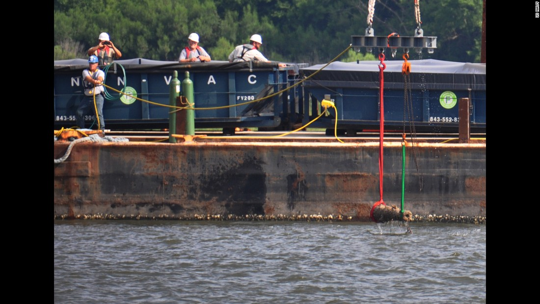The first of four cannons to be removed from the CSS Georgia by U.S. Navy divers is lifted to a barge in the Savannah River on July 15.