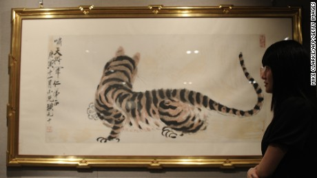 A woman looks at a painting entitled 'Tiger' by Qi Baishi, auctioned in Hong Kong on March 4, 2010. Qi's works were among those forged by a Chinese art academy curator from 2004 to 2010.
