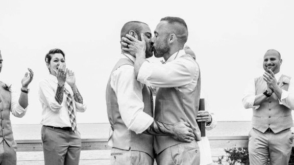 """The timing of the Supreme Court ruling could not have been better for Drew Montalvo, left, and Eric Hanser. A year-and-a-half prior, they set their wedding date for June 27, 2015, without the slightest idea of what was to come the day before. Montalvo is an internationally recognized DJ, but he is in the process of being known by a different name. In what he describes as a progressive effort, Montalvo will be taking his husband's last name. They said """"I do"""" on the barrier island of Fire Island Pines in New York, as captured by <a href=""""http://www.lotusweddings.net/"""" target=""""_blank"""" target=""""_blank"""">Lotus Wedding Photography</a>."""