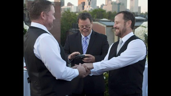 """After 13 years together, Greg Smith, left, and Jack O'Leary, right, officially wed in Boston on their anniversary, June 6, 2015. The ceremony was officiated by O'Leary's twin brother Tom O'Leary, center, captured by <a href=""""http://www.lisasloupe.com/"""" target=""""_blank"""" target=""""_blank"""">Lisa's Loupe Photography</a>. After the wedding they took the celebration to Paris where they had a second ceremony during Paris Gay Pride."""