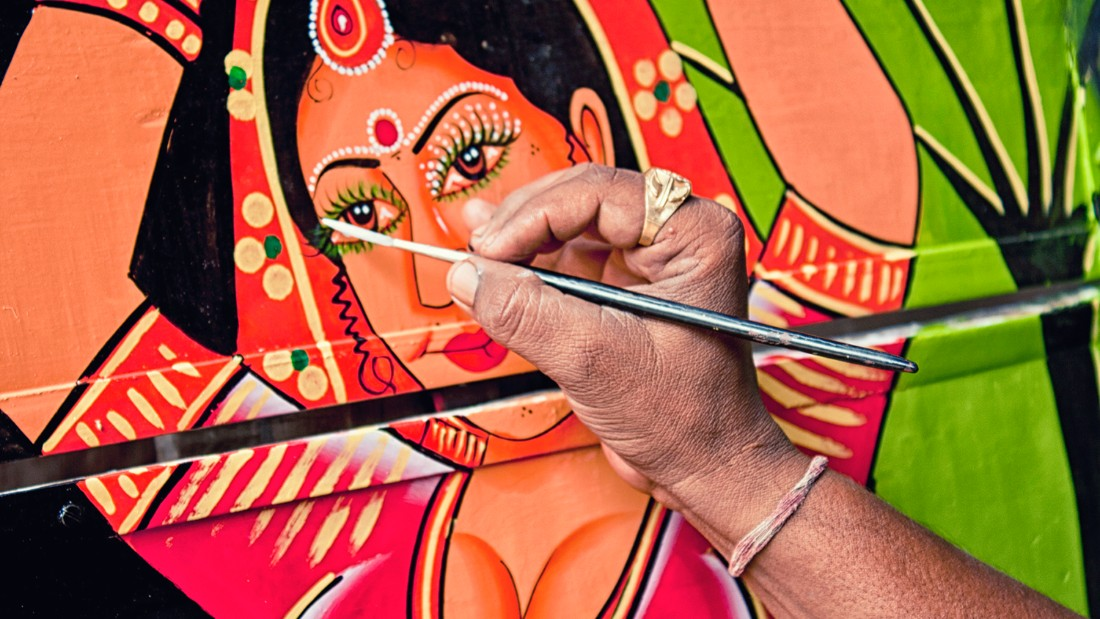 Raja Gharu painting the back of a truck.