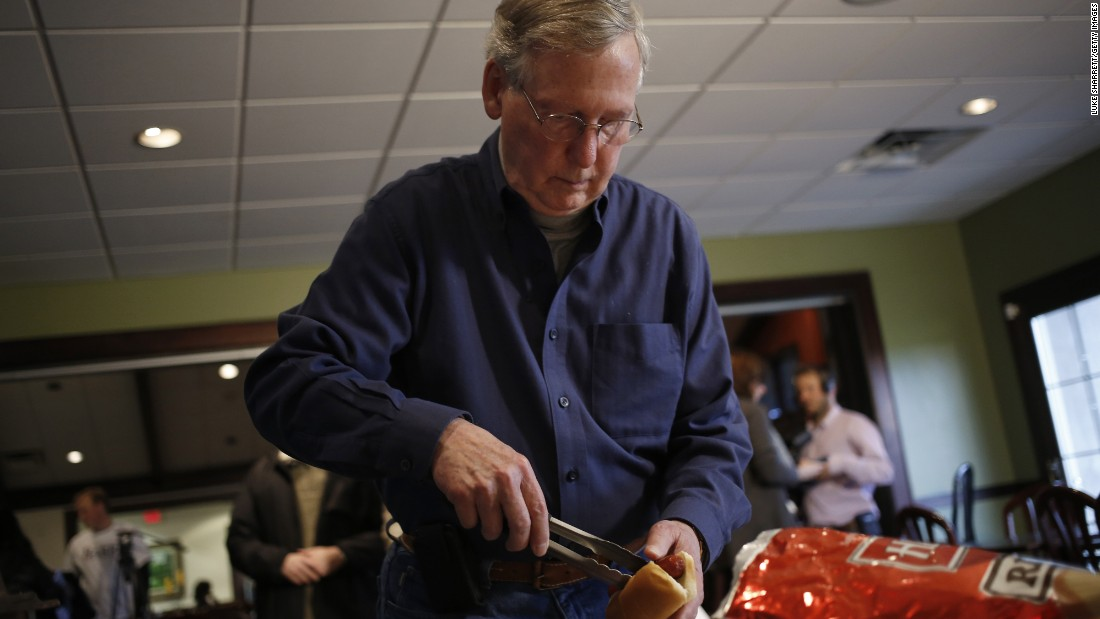 Then-Senate Minority Leader Mitch McConnell, R-Kentucky, serves himself a hot dog after speaking at a campaign rally and hot dog roast at the Old Silo Golf Course and Clubhouse on November 1, 2014, in Mount Sterling, Kentucky.