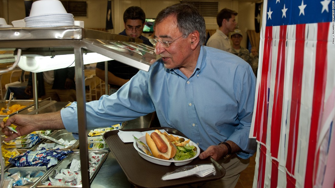 Then-U.S. Secretary of Defense Leon Panetta reaches for a packet of mustard and relish as he takes a hot dog for lunch during his visit to Camp Victory in Baghdad on July 11, 2011.
