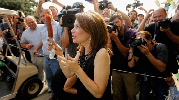 Then-Republican presidential candidate Rep. Michele Bachmann (R-MN) shows off her foot-long corn dog as photographers take her picture at the Iowa State Fair August 12, 2011 in Des Moines, Iowa.