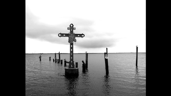 """A cross in the water off Shell Beach, Louisiana, honors victims of Katrina who were from St. Bernard Parish. According to FEMA, Katrina was """"the single most catastrophic natural disaster in U.S. history."""""""
