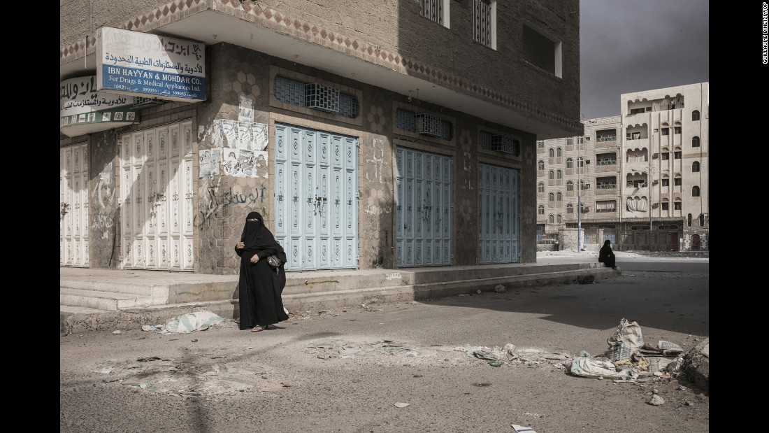 A woman walks in what seems to be a mostly deserted area of the city.