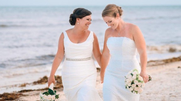 """Long Beach, New York, couple Lauren, left, and Christine Rapkin smile on their wedding day June 25, 2015, in Puerto Morelos, Mexico. They have been together for eight years and wed the day before the landmark Supreme Court decision. Christine is a critical care nurse and Lauren is an event planner and together they enjoy kayaking, beach volleyball and hiking with their dog. Photo courtesy<a href=""""http://nicolebarrphotography.com/"""" target=""""_blank"""" target=""""_blank""""> Nicole Barr Photography.</a>"""