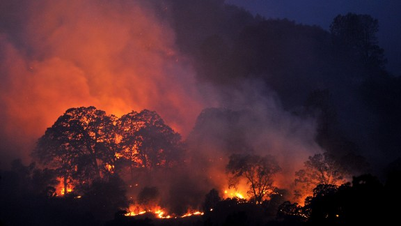 Trees and brush burn while firefighters battle the Wragg Fire near Winters, California, on Thursday, July 23. The fast-moving wildfire had scorched almost 7,000 acres in Napa and Sonoma counties, authorities said.