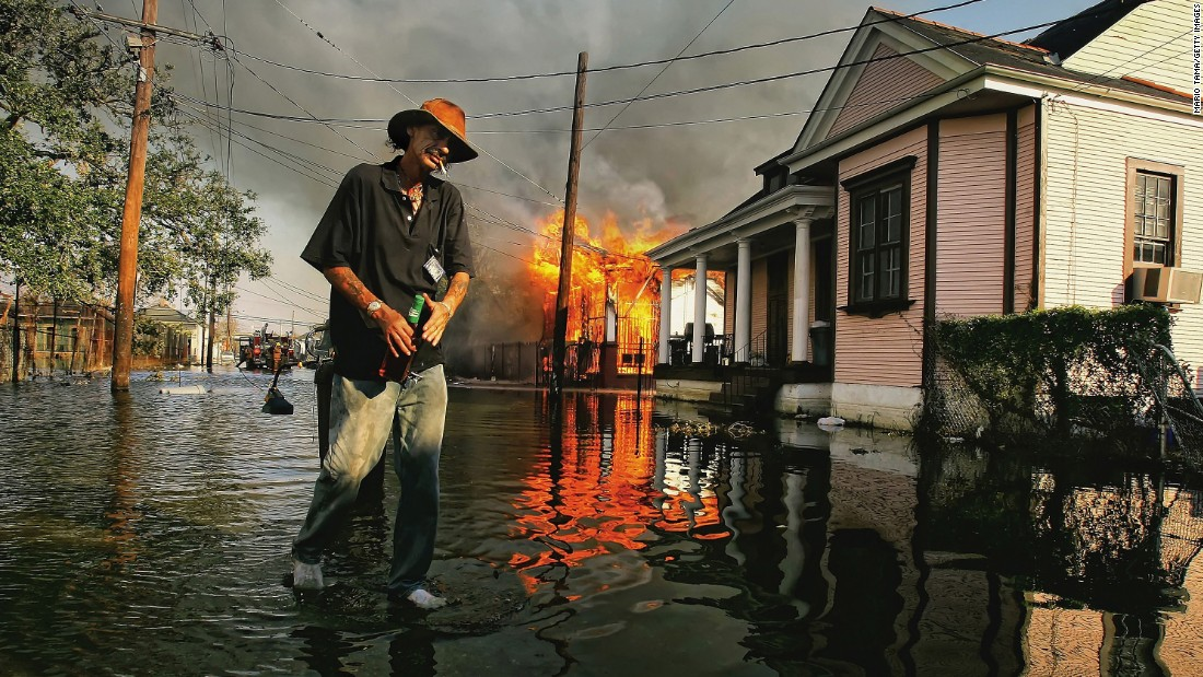 Robert Fontaine walks past a burning house fire in New Orleans' Seventh Ward on September 6, 2005.