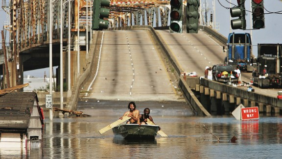 Two men paddle through the streets past the Claiborne Bridge in New Orleans on August 31, 2005.