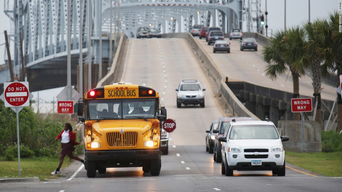A school bus drops off a student in front of the Claiborne Bridge on May 12, 2015.