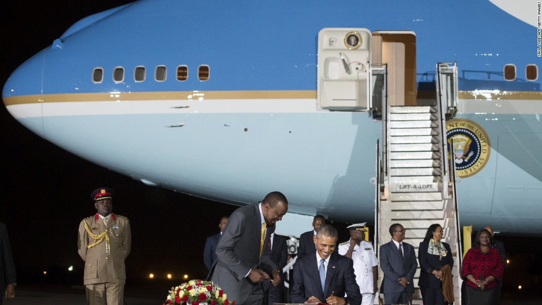 Obama signs a guest book alongside Kenyatta upon arrival at Kenyatta International Airport in Nairobi on Friday, July 24.