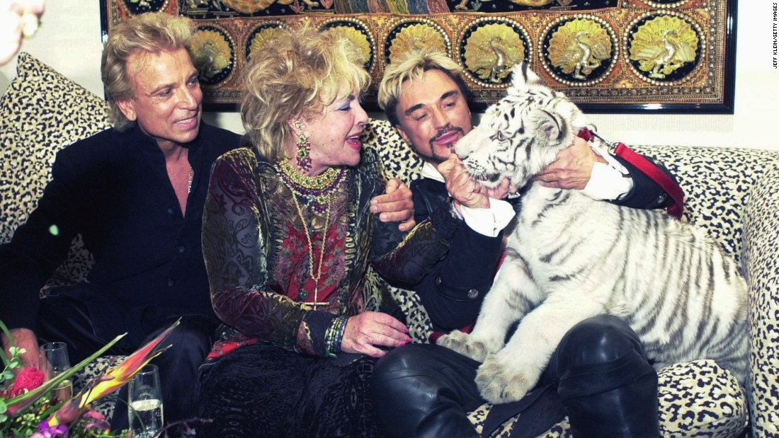 Late actress Elizabeth Taylor (center) greets Atlas, a five-month-old white Siberian tiger with entertainers Siegfried and Roy following their show at the Mirage Hotel and Casino on December 31, 2001.