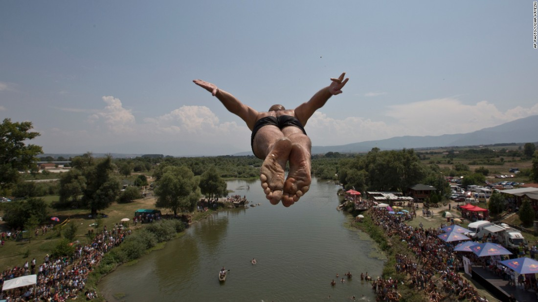 A diver leaps from the Saint Bridge into the Drini i Bardhe river during the annual high diving competition near the town of Gjakova, 100 kilometers south of the Kosovan capital of Pristina, on July 26, 2015. 27 divers from Kosovo took part in the open-air contest this year.