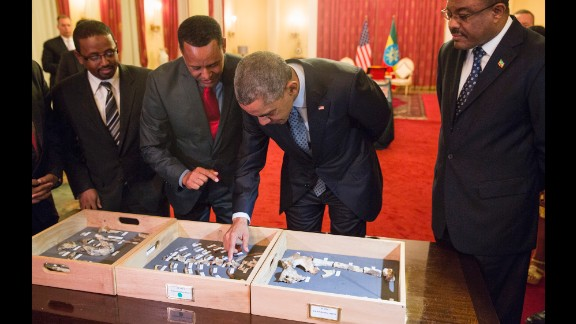 """Desalegn, right, watches as Obama touches the """"Lucy"""" exhibit at the National Palace on July 27. """"Lucy"""" is made up of several hundred pieces of bone representing 40% of a female Australopithecus afarensis, a human-like species estimated to have lived in Ethiopia 3.2 million years ago."""