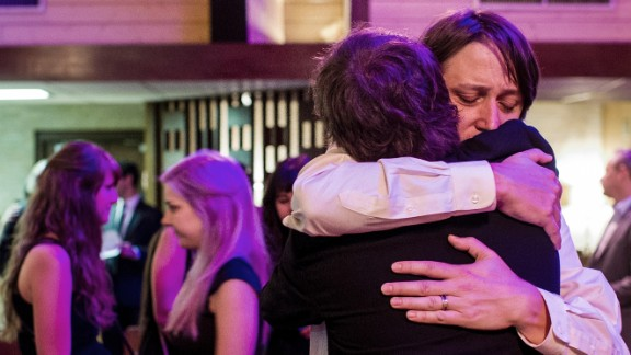 Jason Brown, husband of Jillian Johnson, hugs a guest following the funeral service.