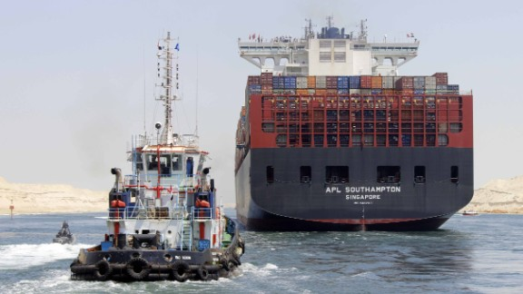 """Boats, including a container ship, cross the new waterway of the Suez Canal on July 25, 2015, in the Egyptian port city of Ismailia, east of Cairo. Egypt started the first trial run of its """"new Suez canal,"""" officials said, ahead of the new shipping route's formal inauguration on August 6, 2015 -- a year after construction began."""