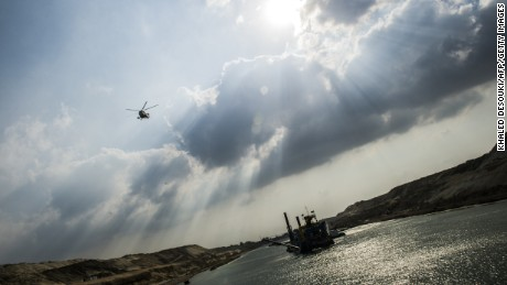 An Egyptian army helicopter flies over a dredger at work on the new waterway of the Suez canal on June 13, 2015, in the port city of Ismailia, east of the capital Cairo.