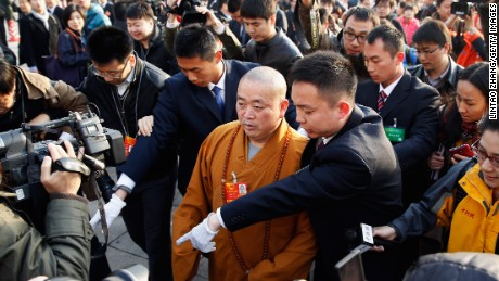 Shi Yongxin (C) Abbot of Shaolin Temple, arrives at The Great Hall Of The People to attend the opening session of the annual National People's Congress at Great Hall of the People on March 5, 2013 in Beijing.