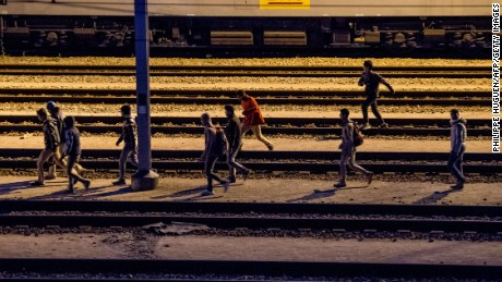 Migrants walk along railway tracks at the Eurotunnel terminal on July 28, 2015 in the Calais-Frethun station in the French port town of Calais.