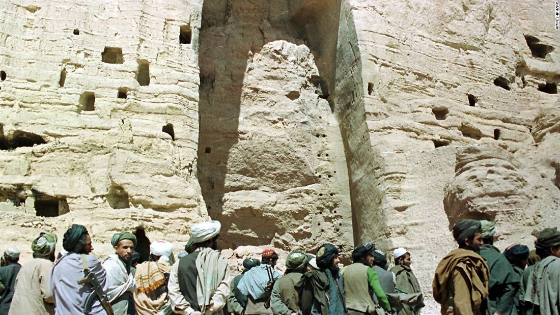 In March 2001, Taliban soldiers stand at the base of the mountain alcove where a Buddha statue once stood 170 feet high in Bamiyan, Afghanistan. The Taliban destroyed two 1,500-year-old Buddha figures in the town, saying they were idols that violated Islam.
