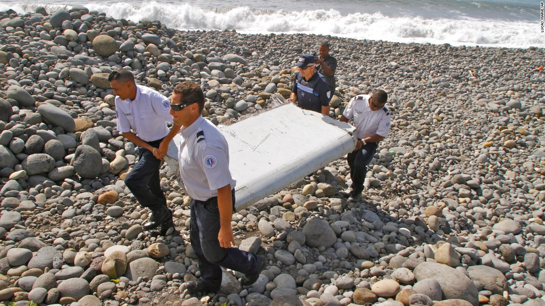 French police officers carry the plane debris on July 29. Experts say the metallic object may be a piece of a moving wing surface, known as a flaperon, from a Boeing 777.