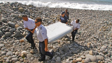 "In this photo dated Wednesday, July 29, 2015, French police officers carry a piece of debris from a plane in Saint-Andre, Reunion Island. Air safety investigators, one of them a Boeing investigator, have identified the component as a ""flaperon"" from the trailing edge of a Boeing 777 wing, a U.S. official said. Flight 370, which disappeared March 8, 2014, with 239 people on board, is the only 777 known to be missing. (AP Photo/Lucas Marie)"