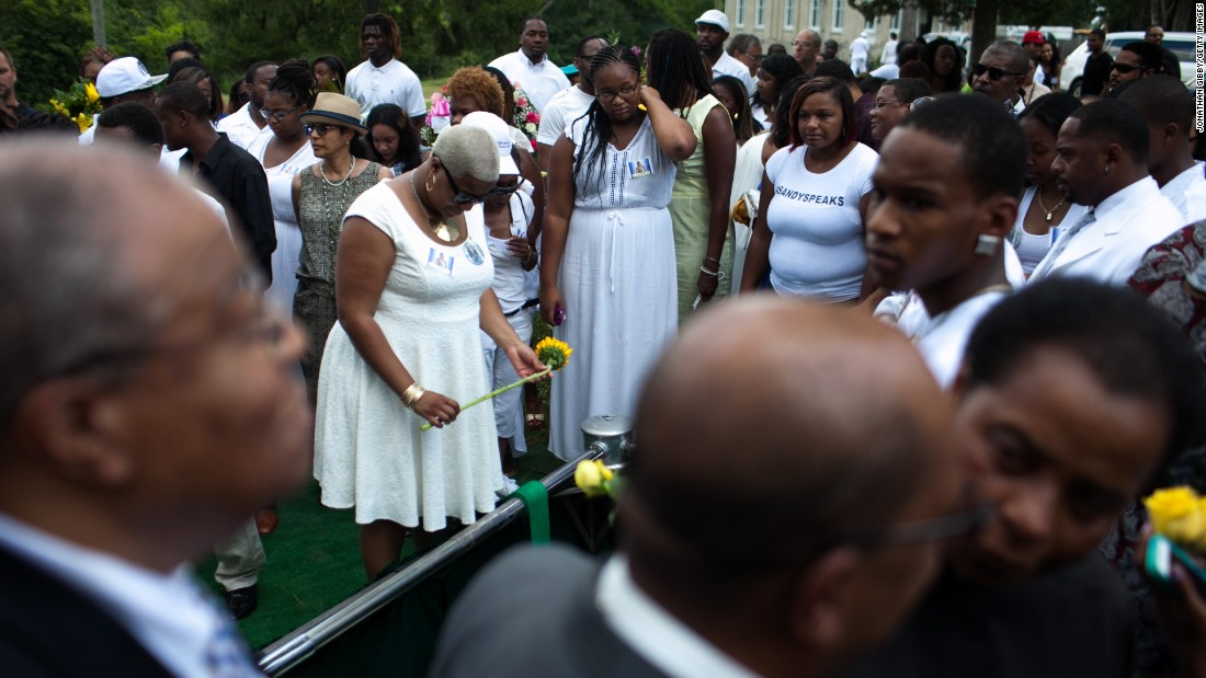 "Shavon Bland holds a flower over her sister's gravesite in Willow Springs, Illinois, on Saturday, July 25. <a href=""http://www.cnn.com/2015/07/20/us/gallery/sandra-bland-texas-jail-death-vigil/index.html"" target=""_blank"">Sandra Bland</a> was arrested on July 10 for allegedly assaulting an officer during a routine traffic stop. On July 13, she was found dead in her jail cell. Police say the 28-year-old hanged herself with a plastic bag. Her family disputes that."