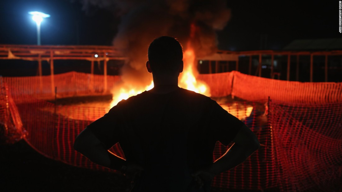 Doctors Without Borders staffer Alex Eilert Paulsen watches as mattresses and bed frames burn at the Ebola Treatment Unit in Paynesville, Liberia, on January 31, 2015. The organization reduced its number of beds from 250 to 30 as gains were made in battling the virus.