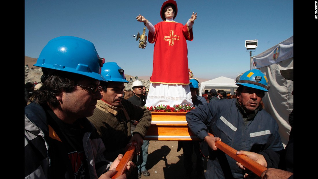 Miners carry an effigy of Saint Lorenzo, the patron saint of miners, before a Mass outside the collapsed mine on August 10.