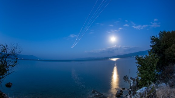 """Stojan Stojanovski was near the Ohrid """"St. Paul the Apostle"""" Airport to photograph the blue moon.  """"The moon was very bright,"""" he said. He waited for planes to take off from the airport to get this long exposure shot."""