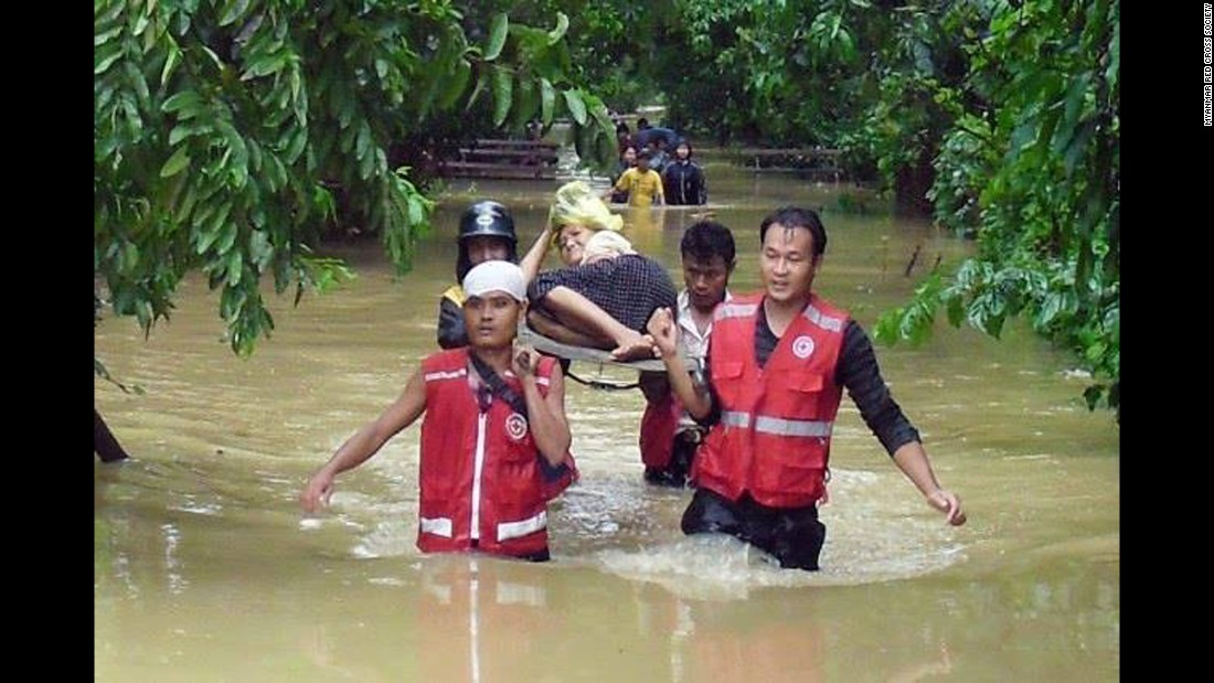 Members of the Myanmar Red Cross Society help carry a woman through floodwaters after the heavy rains over the weekend.