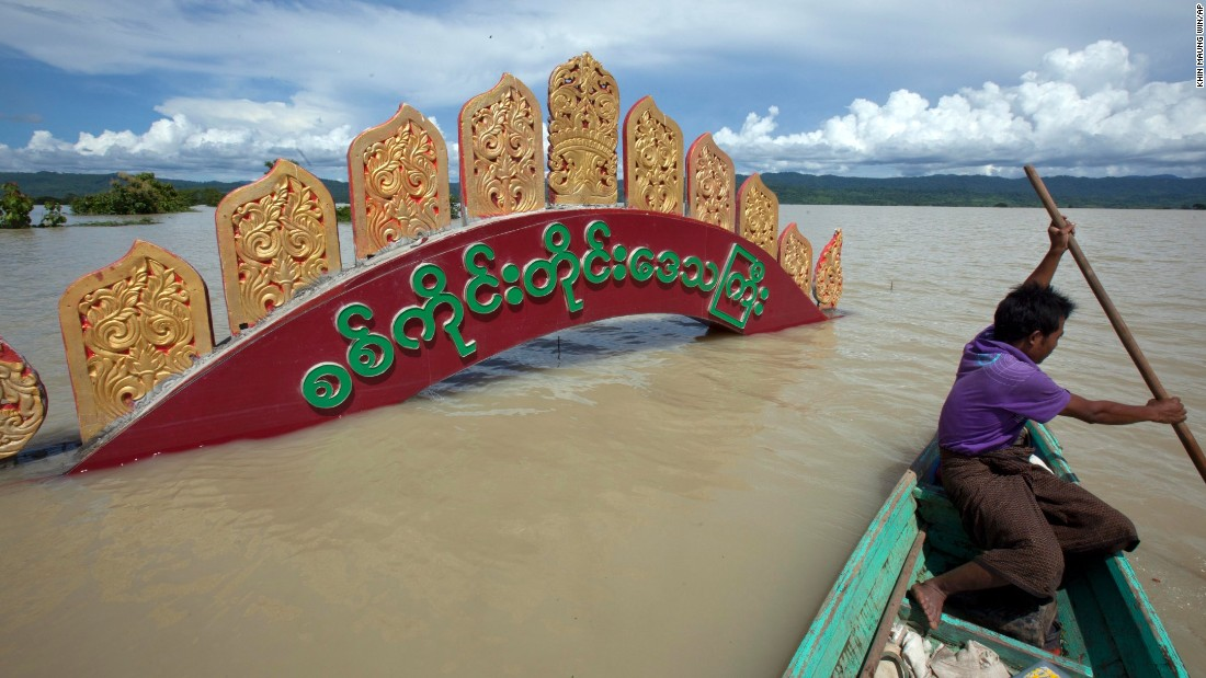 A man rows by the entrance signboard of Kalay, which is submerged in water.