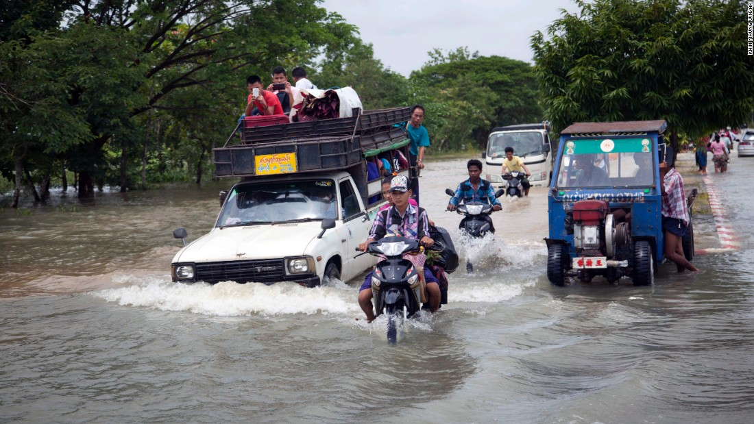 Vehicles loaded with flood victims drive through a deluged road in Bago, 50 miles northeast of Yangon, the largest city in the Asian nation.